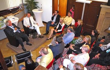Jürgen Schneider erzählt in der Kanzlei Cäsar-Preller in Wiesbaden, das Publikum lauscht.
