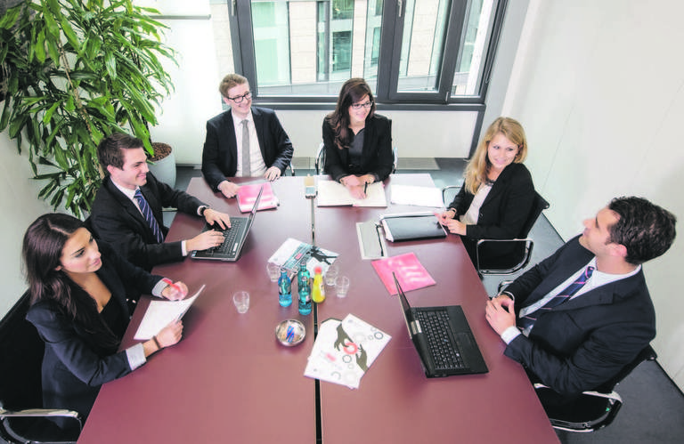Trainees und Praktikanten bei Jones Lang LaSalle aus den Bereichen Office Leasing, Office Investment, Retail Leasing, Portfolio Investment und Human Resources an einem Tisch.