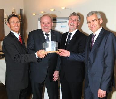 Volker Skroblies (2.v.l.) erhielt zum Abschied ein Model des neuen Kaufhos in Lübeck von den Vorständen Marcel Sonntag (ganz links) und Dr. Uwe Heimbürge (ganz rechts) sowie dem Aufsichtsratsvorsitzenden Michael Voigt.