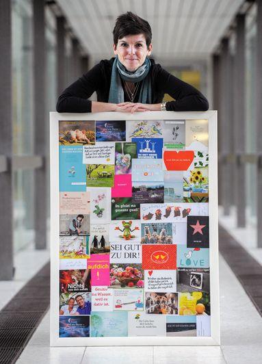 Petra Zahrt mit einer Collage von Genesungswünschen, die sie von ihrer Familie und Freunden erhalten hat. Das Bild hängt jetzt in ihrem Büro über ihrem Schreibtisch.
