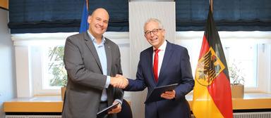 Wisag-Chef Michael Wisser und Gerd Hoofe, Staatssekretär im Bundesverteidigungsministerium, besiegeln die Personalpartnerschaft von Wisag und Bundeswehr.