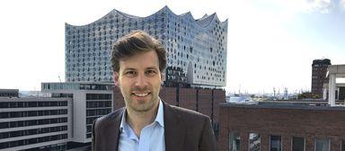 Exporo-Immobilienchef Julian Oertzen über den Dächern von Hamburg. Im Hintergrund: die Elbphilharmonie.