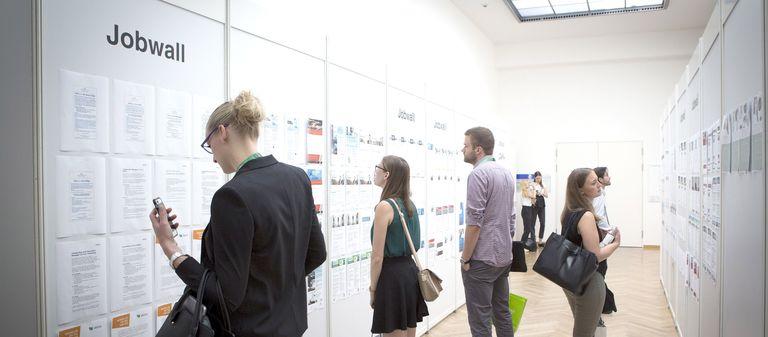 Besucher des IZ-Karriereforums studieren Stellenannoncen.